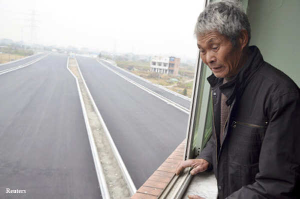 An old man looks down from his house which stands alone in the middle of a newly built road in Wenling, Zhejiang province.