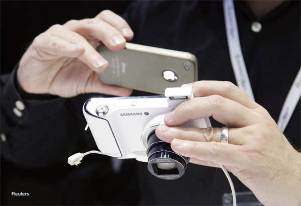 A man takes a picture of a Samsung Galaxy Camera during press preview day before the official start of the IFA consumer electronics fair in Berlin, in this August 30, 2012 file picture.