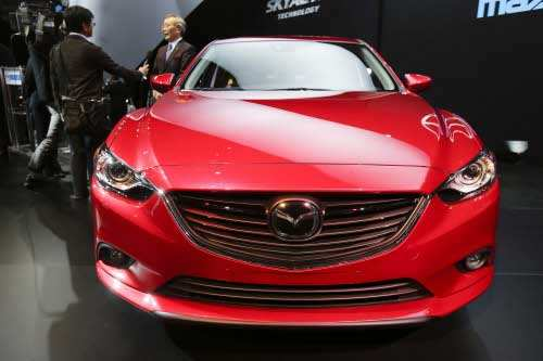 Mazda CEO Takashi Yamanouchi is interviewed while the Mazda6 is shown during it's North American debut at the LA Auto Show in Los Angeles, Thursday, November 29, 2012. (AP photo)