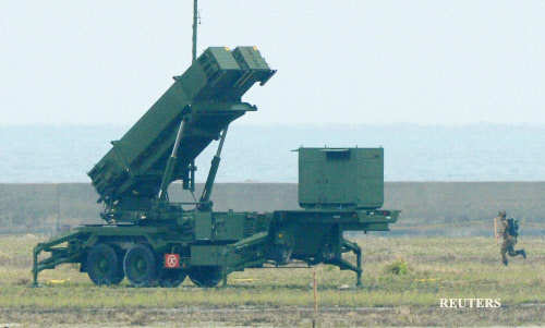 A member of the Japan Self-Defence Forces runs toward a Patriot Advanced Capability-3 (PAC-3) missiles unit in Ishigaki on Japan's southern island of Ishigaki Island, Okinawa prefecture, in this photo taken by Kyodo on December 12, 2012.