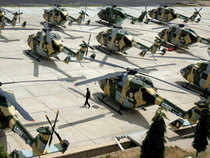 A security official walks among a group of Dhruv Helicopters of India's Hindustan Aeronautics Limited (HAL) parked on the tarmac at The HAL Helicopter Division in Bangalore. (AFP)