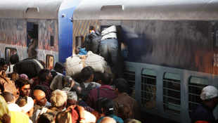 Devotees returning from Maha Kumbh jostle to get in a coach of a train at the main railway station of Allahabad on Monday, February 11, 2013.
