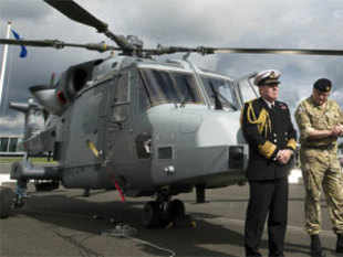 This file photography taken on July 11, 2012 shows military officials next to a new AgustaWestland AW159 Wildcat helicopter at the Farnborough International Airshow in Hampshire, southern England.