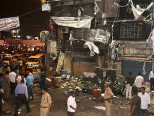 People and police officers stand at the spot after a bomb blast in Hyderabad, India, Thursday, Feb. 21, 2013. AP