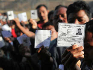 Voters display their identity cards as they stand in queue to cast their votes at a polling station in Byrnihat, in the northeastern Indian state of Meghalaya, Saturday, Feb. 23, 2013. AP