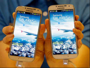 A model shows Samsung Electronics Co.'s latest Galaxy S4 smartphones during its unveiling ceremony in Seoul, South Korea, Thursday, April 25, 2013. AP