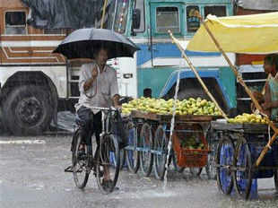 A man holds his umbrella and cycles past a fruit vendor as it rains in Allahabad on July 1, 2013.