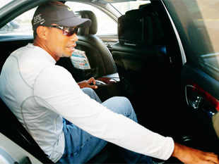 Tiger Woods gets into a car after arriving at the IGI airport in New Delhi on Monday.