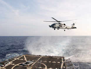 Handout picture of A U.S. Navy SH-60R Seahawk helicopter takes off from the destroyer USS Pinckney in the Gulf of Thailand, to assist in the search for missing Malaysian Airlines flight MH370.