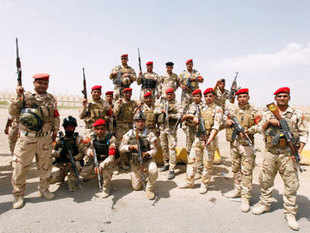 """Expressing alarm over the conflict in Iraq on Thursday, Russia said it had long predicted that US and British """"adventurism"""" there would end badly.In pic: Members of Iraqi security forces pose as they guard volunteers who have joined the Iraqi Army to fight against the predominantly Sunni militants, who have taken over Mosul and other Northern provinces, travelling in army trucks in Baghdad."""