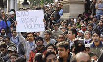 A man holds up a banner as Indian students and supporters rallied in Melbourne.
