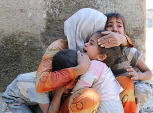 A Syrian woman comforts her children after their house in the Sahour nieghbourhood of the northern Syrian city of Aleppo was bombed. (Getty Images/AFP file photo)