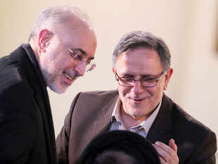 Iran's head of Atomic Energy Organisation (IAEO) Ali Akbar Salehi (L) talks with the Head of the Central Bank of Iran, Valiollah Seif, as they arrive for a press conference of Iranian President on January 17, 2016 in the capital Tehran after international sanctions on Iran were lifted.