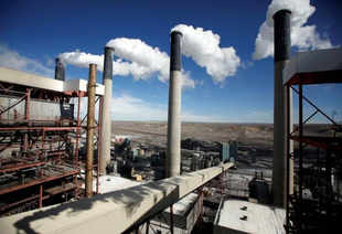 Steam rises from the stakes of a coal-fired plant.