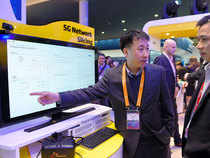 A technician explains to visitors the Network 5G operation at the SK Telecom's stand at the Mobile World Congress in Barcelona on February 22, 2016, on the first day of the world's biggest mobile fair that runs to February 25.