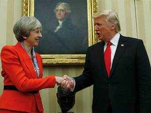 May, dressed in red, was greeted in person by Trump when she arrived at the White House.