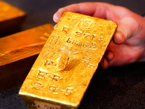Gold inched down on Monday on a stronger dollar, moving away from a 5-month high hit in the previous session.