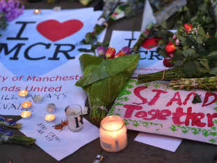 Messages and floral tributes are seen in Albert Square in Manchester, northwest England
