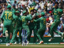 Pakistan's Mohammad Amir celebrates with teammates after taking the wicket of India's Virat Kohli.