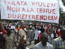 File Photo: Protesters walk under a banner reading 'No to the referendum' as they demonstrate against a referendum on a constitution's revision draft.
