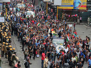 Supporters of the Gorkha Janmukti Morcha (GJM) rally as they carry bodies of protesters who were killed in clashes with security forces on Saturday, in Darjeeling.
