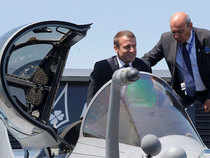 French President Emmanuel Macron exits the cockpit of a Rafale jet fighter helped by Dassault Aviation CEO Eric Trappier (R) during his visit at the 52nd Paris Air Show in Le Bourget, north of Paris