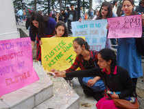 People holding placards and lighting candles to seek justice for a 16-year-old girl