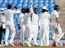 Sri Lanka's Malinda Pushpakumara celebrates with teammates after taking the wicket of India's Ajinkya Rahane.