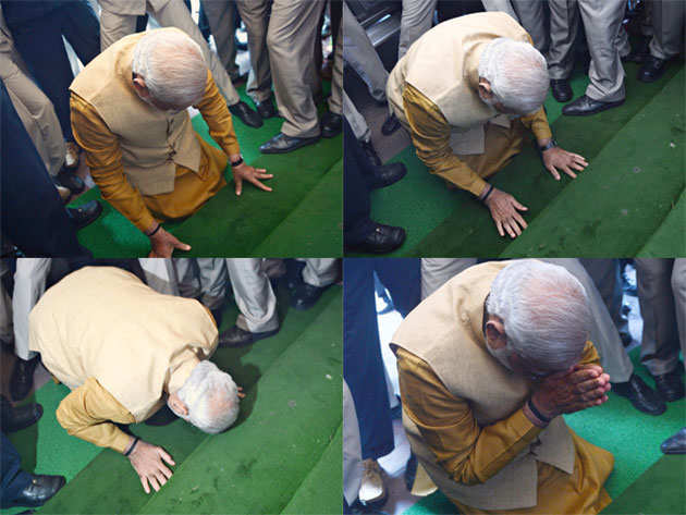 Narendra Modi touching his forehead on the ground outside the Parliament