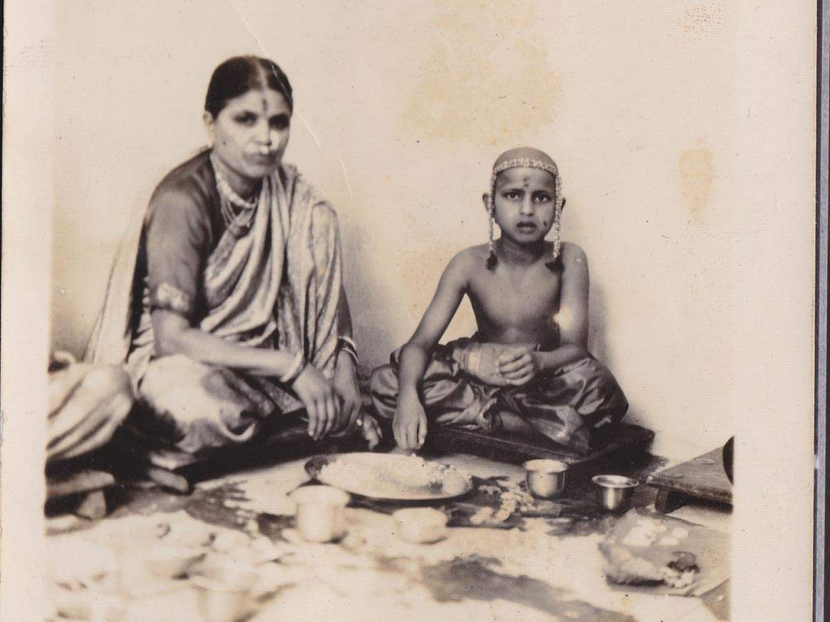 """""""This picture of my mother and I was taken at my thread ceremony. I was growing up. This ritual signifies the last time a son eats from his mother's plate."""" – Col. Deodutta Rajwade, Nagpur, 1930s"""