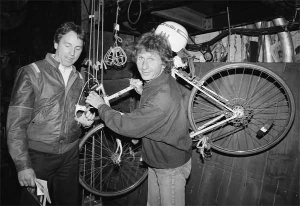 In this May 16, 1985, file photo, actor John Ritter, left, checks out the bicycle of fellow actor Rene Auberjonois backstage at the Eugene O'Neill Theatre in New York following a performance of the Broadway musical, 'Big River: The Adventures of Huckleberry Finn'. 