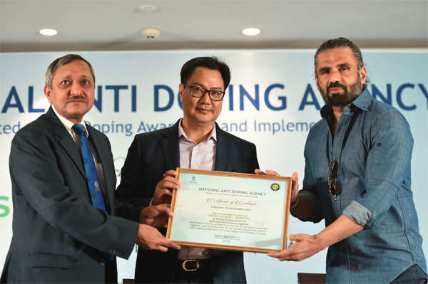 Union Minister for Youth Affairs and Sports Kiren Rijiju (c) felicitates Bollywood actor Suniel Shetty (r) as he is appointed as the brand ambassador of National Doping Agency (NADA), in New Delhi.