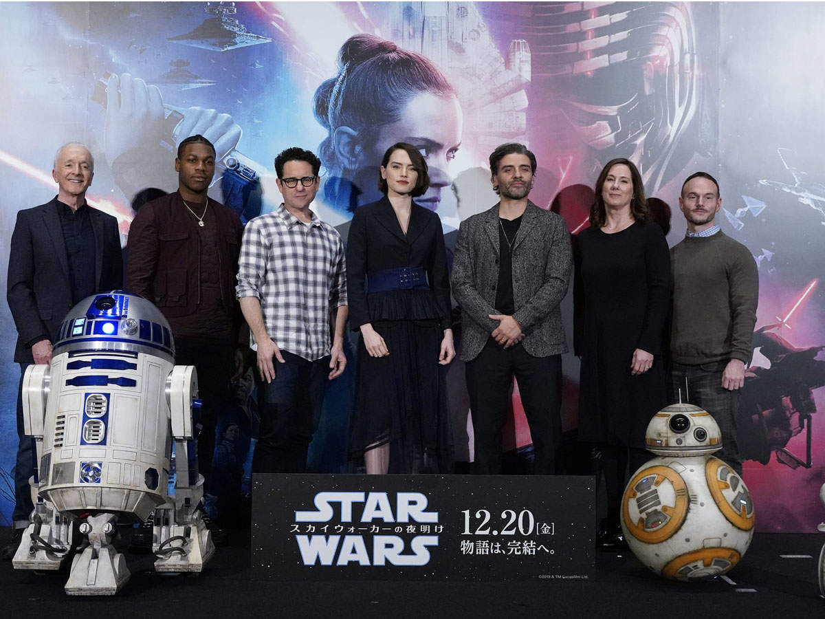 (L-R) Anthony Daniels, John Boyega, J.J. Abrams, Daisy Ridley, Oscar Isaac, Kathleen Kennedy, and Chris Terrio pose for photos with Star Wars characters R2-D2, BB-8, and D-O at the press conference for 'Star Wars: The Rise of Skywalker'.