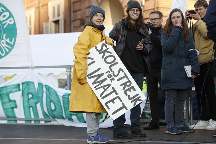 ​Greta Thunberg holds a sign with writing reading in Swedish 'School strike for the climate' as she attends a climate march in Italy​​​.