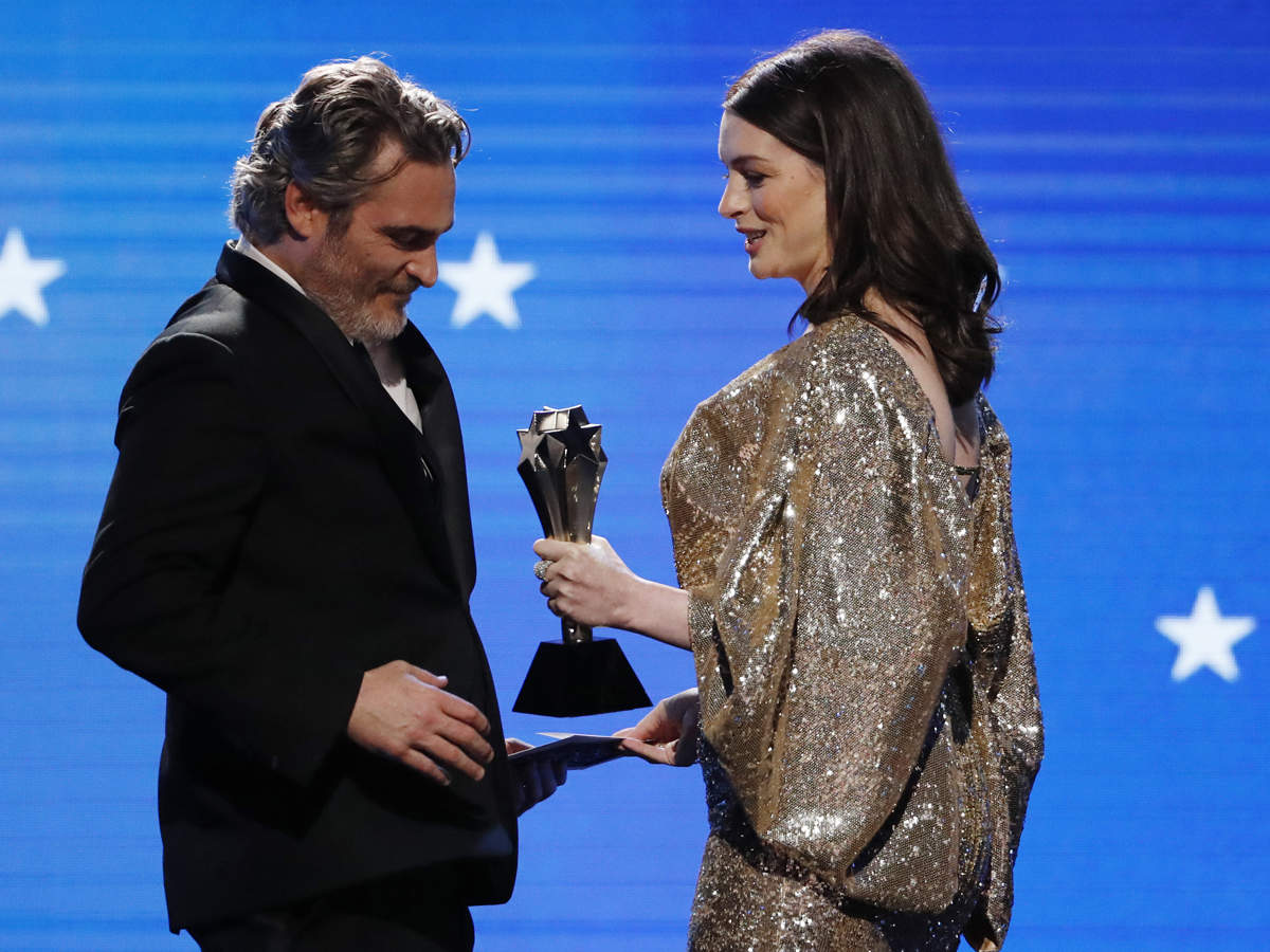 Anne Hathaway (R) presents the Best Actor award to Joaquin Phoenix for his role in 'Joker.'