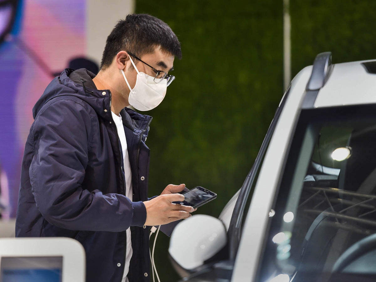 A visitor wears a mask as he looks at cars on display at the Auto Expo 2020 in Greater Noida.