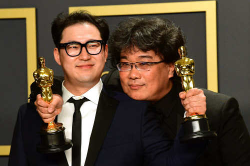 'Parasite' writers Han Jin-won (L) and Bong Joon-ho pose in the press room with the Oscars for 'Parasite' during the 92nd Oscars at the Dolby Theater in Hollywood, California.