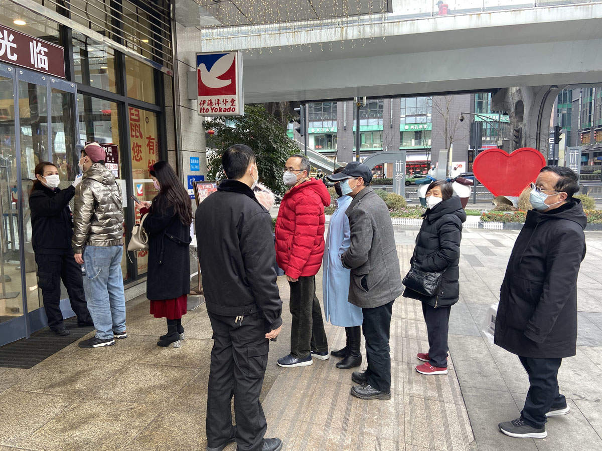 Wearing masks, people lined up for temperature checks before entering the mall in Chengdu,China.