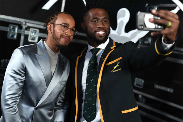 Lewis Hamilton (L) and Laureus World Team of the Year winner Siya Kolisi, captain of the South Africa Men's Rugby team, pose for a selfie during the 2020 Laureus World Sports Awards ceremony.
