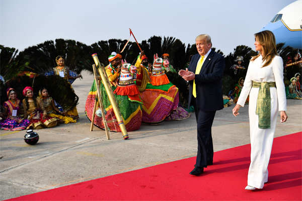 Donald Trump and First Lady Melania Trump are greeted by performers wearing traditional costumes at the Agra Air Base.