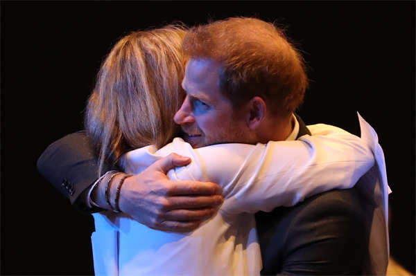 Prince Harry receives a hug as he greets guests at a sustainable tourism summit at the Edinburgh International Conference Centre in Scotland.