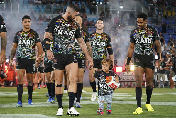 ​Quaden Bayles leads the Indigenous All Stars on to the field with captain Joel Thompson prior to the NRL Indigenous All-Stars vs Maori Kiwis match at CBus Super Stadium on the Gold Coast.​