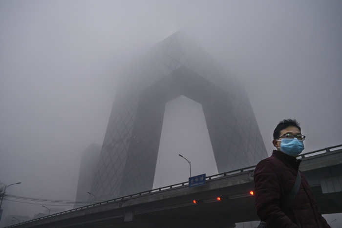 File photo of February 13, 2020: A Chinese man wears a protective mask as he passes near the CCTV building in fog and pollution during rush hour in the central business district in Beijing, China.