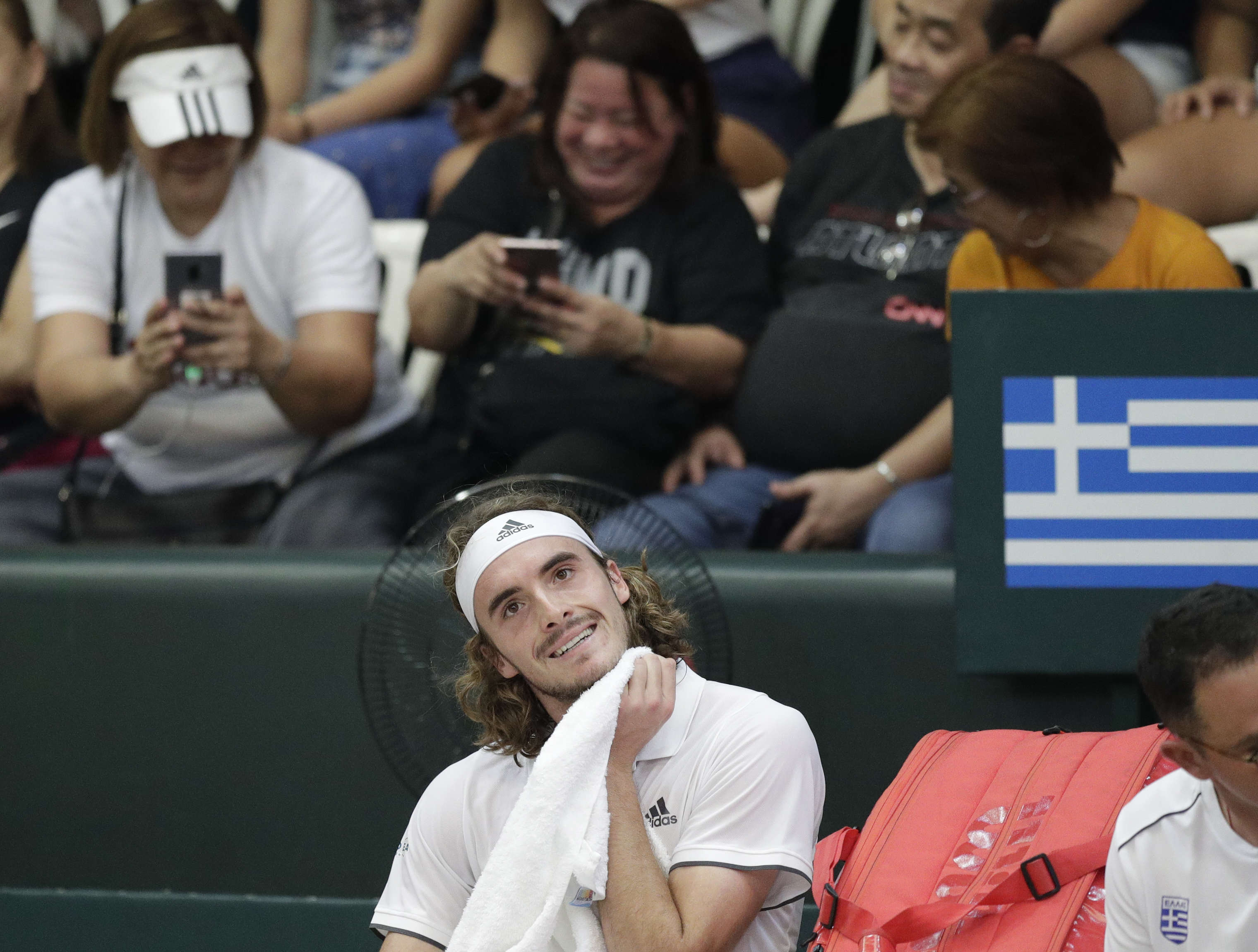Stefanos Tsitsipas of Greece, wipes sweat during his game against Alberto Lim of the Philippines at the Davis Cup World Group II play-offs first round singles match in Manila, Philippines