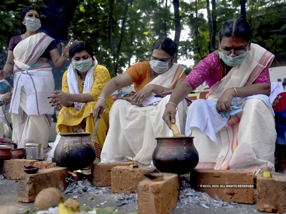 Women wear masks as a precaution against a new coronavirus while cooking a rice dish as an offering during the annual Pongala festival at the Attukal temple in Thiruvananthapuram, Kerala.