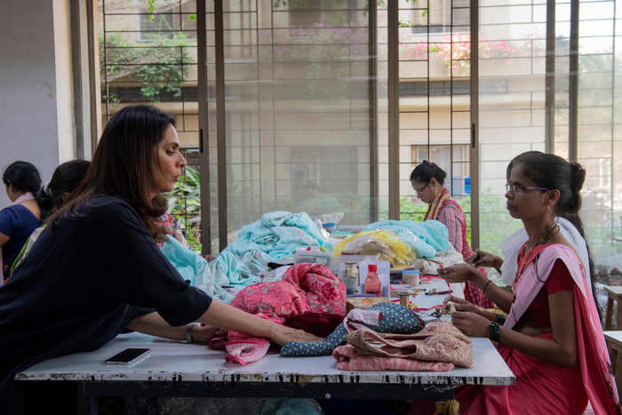 Anita Dongre (L) interacts with a worker at her factory on the outskirts of Mumbai.