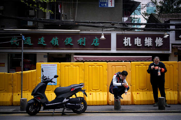 People wearing face masks eat 'Regan Noodle' for breakfast at a residential area blocked by barriers in Wuhan.