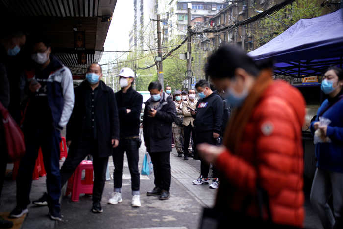 People wearing face masks line-up to pay for their Regan Noodle breakfast in Wuhan.