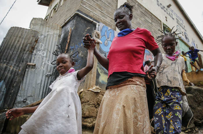 Margaret Andeya takes her daughter Gettrueth Ambio, 12, right, and her neighbor's daughter Jane Mbone, 7, left, back home after having their hair styled in the shape of the new coronavirus at the Mama Brayo Beauty Salon in the Kibera slum, or informal settlement, of Nairobi, Kenya