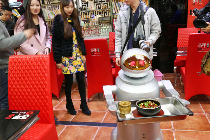File photo of December 2014: A restaurant at Chunxi Road in Chengdu had adopted 10 robots to serve as waiters. Each robot could carry simple dishes and offer simple greetings.